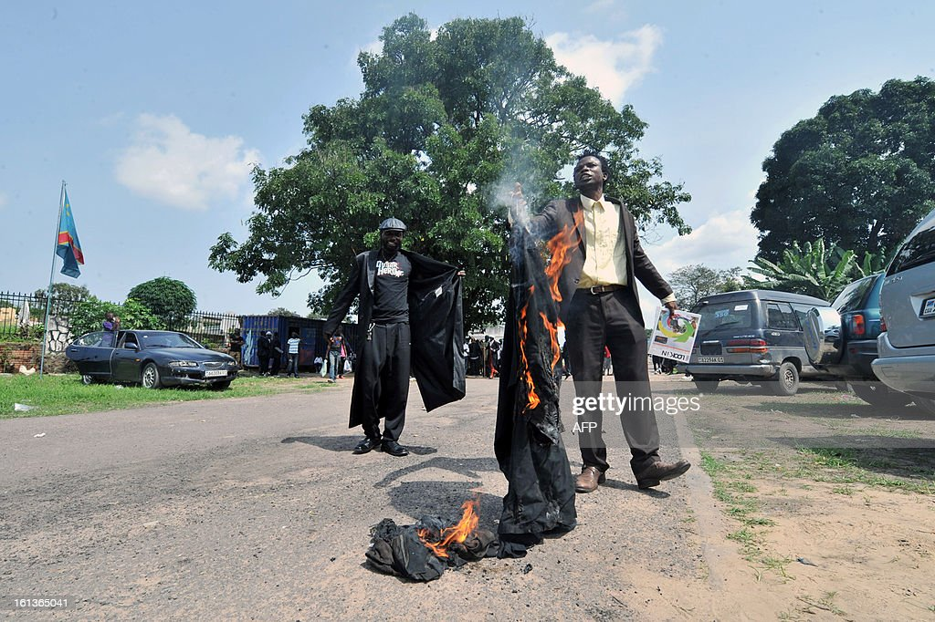 Brand fashion addicts ('Sapeurs' in French) from Kinshasa burn clothes as they take part in a tribute to Stervos Niarcos, on Feburary 10, 2013 on the 18th anniversary of Niarcos' death at the Gombe cemetery in Kinshasa. Niarcos was known as the leader of the 'Sape' movement and the founder of the 'Kitendi' religion, which means clothing in local Lingala language. AFP PHOTO / JUNIOR D. KANNAH