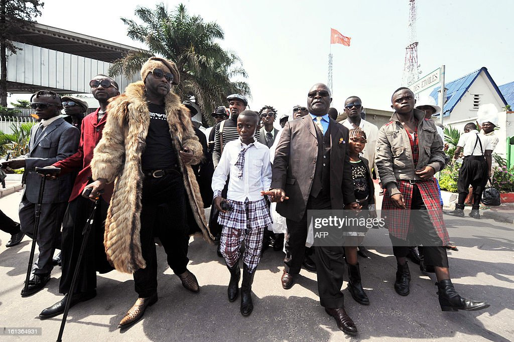 Brand fashion addicts ('Sapeurs' in French), members of 'DR Congo Leopard' from Brazzaville, arrive with leader Ben Mukasha (C) to take part in a tribute to Stervos Niarcos, on Feburary 10, 2013 on the 18th anniversary of Niarcos' death at the Gombe cemetery in Kinshasa. Niarcos was known as the leader of the 'Sape' movement and the founder of the 'Kitendi' religion, which means clothing in local Lingala language. AFP PHOTO / JUNIOR D. KANNAH