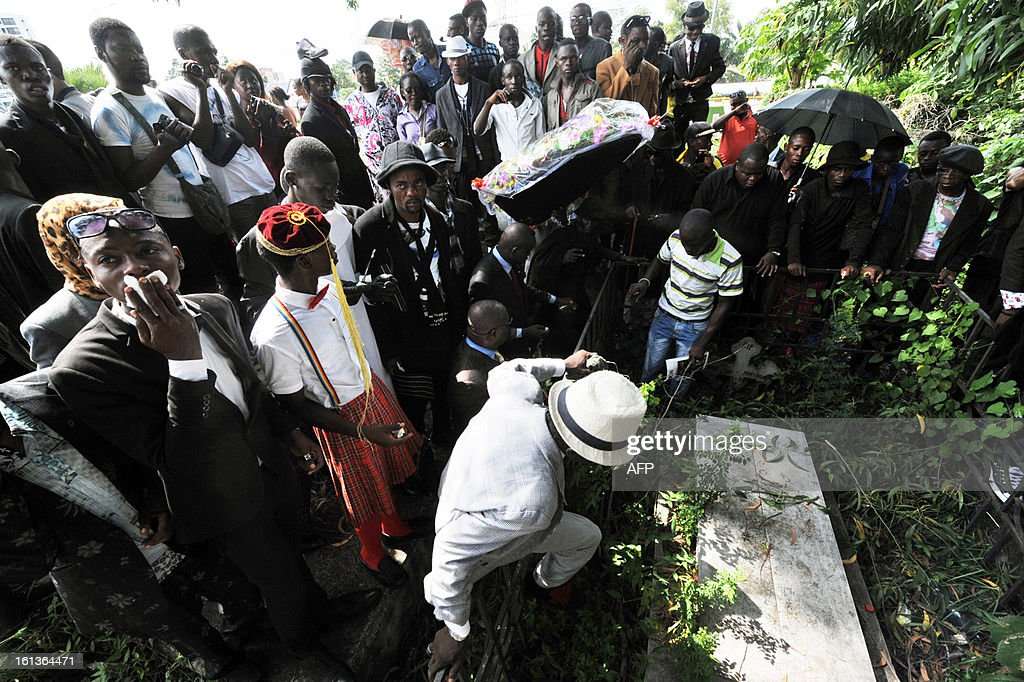 Brand fashion addicts ('Sapeurs' in French) pay a tribute to Stervos Niarcos next to his grave, on Feburary 10, 2013 on the 18th anniversary of Niarcos' death at the Gombe cemetery in Kinshasa. Niarcos was known as the leader of the 'Sape' movement and the founder of the 'Kitendi' religion, which means clothing in local Lingala language.