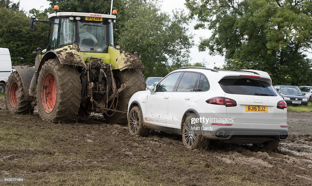 A brand new Porsche 4x4 is towed by a tractor as festival goers leave the Glastonbury Festival 2016 at Worthy Farm, Pilton on June 26, 2016 near Glastonbury, England. The Festival, which Michael Eavis started in 1970 when several hundred hippies paid just £1, now attracts more than 175,000 people.