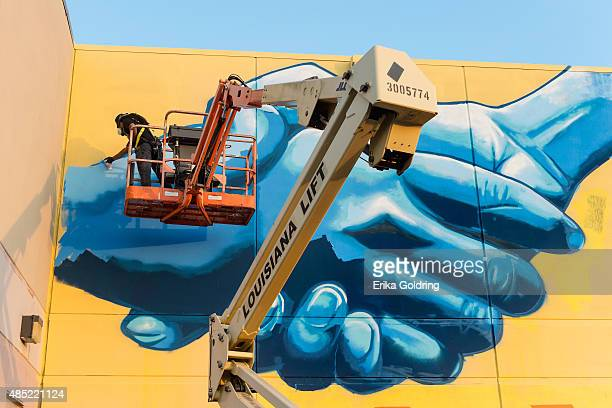 Brandan 'BMike' Odums nears completion of The Wall of Peace mural at The Grand Theater on August 25 2015 in New Orleans Louisiana The timing of the...