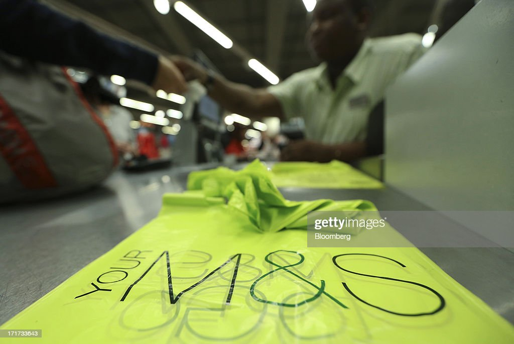 Branded carrier bags sit on a check-out as a customer pays for their purchases inside a Marks & Spencer Group Plc (M&S) food hall in the Westfield Stratford City retail complex in London, U.K., on Thursday, June 27, 2013. U.K. retail sales rose more than economists forecast in May as consumers spent more online and food sales increased at their fastest pace for more than two years. Photographer: Chris Ratcliffe/Bloomberg via Getty Images