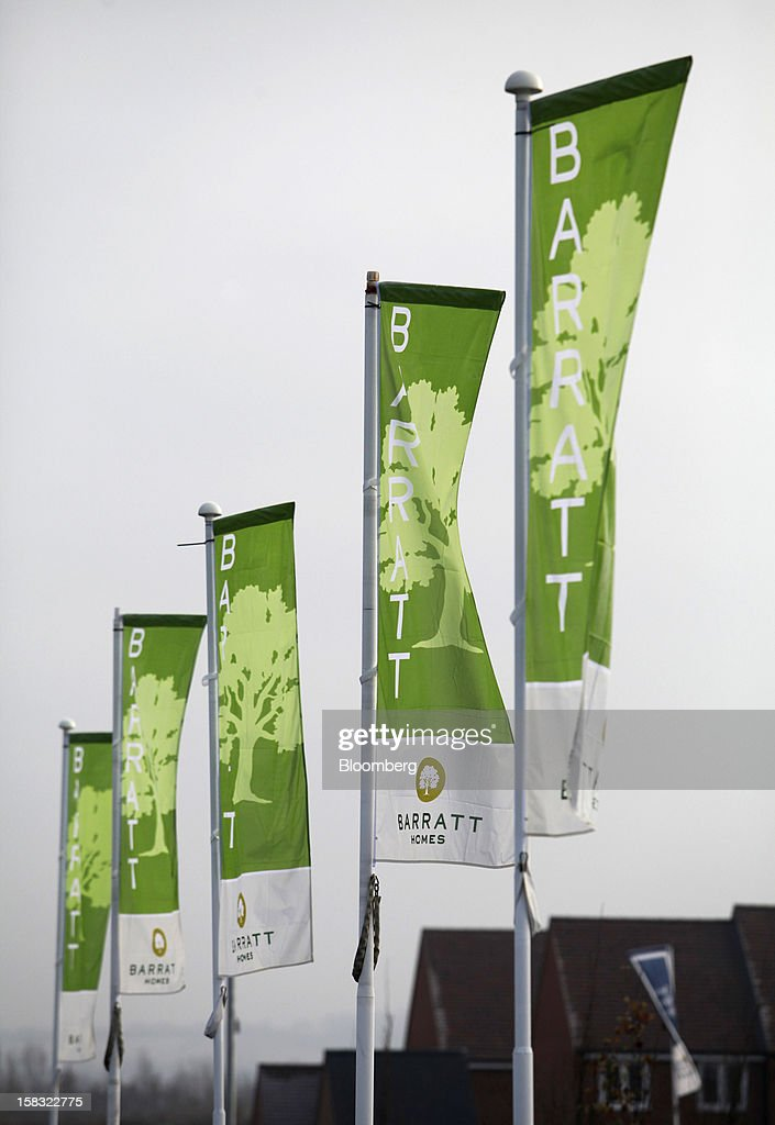 Branded flags fly at a Barratt Developments Plc construction site for residential housing in Bedford, U.K., on Thursday, Dec. 13, 2012. Barratt Developments Plc, the U.K.'s largest homebuilder by volume, said advance sales rose 21 percent as government initiatives to boost homebuilding lifted private reservations in the autumn selling season. Photographer: Chris Ratcliffe/Bloomberg via Getty Images