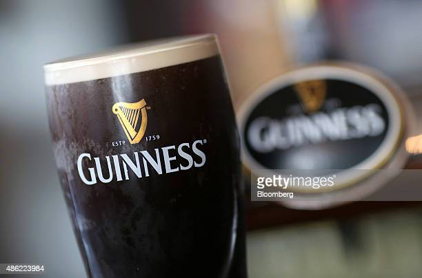 A branded pint of Guinness stout sits on the bar at The Honor Oak public house operated by Punch Taverns Plc in London UK on Wednesday Sept 2 2015...
