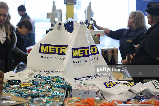 Branded plastic bags hang near the cash tills at a Metro AG Cash Carry supermarket store in Moscow Russia on Wednesday March 5 2014 Metro AG...