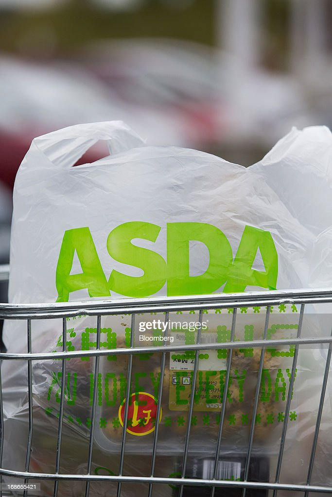 A branded shopping bag containing a customer's purchases sit in a shopping cart outside an Asda supermarket store, operated by Wal-Mart Stores Inc., in the Wandsworth borough of London, U.K., on Monday, May 13, 2013. Asda, the U.K. supermarket chain owned by Wal-Mart Stores Inc., said sales rose 4.5 percent last year and it's investing 700 million pounds ($1 billion) into stores and online operations. Photographer: Jason Alden/Bloomberg via Getty Images