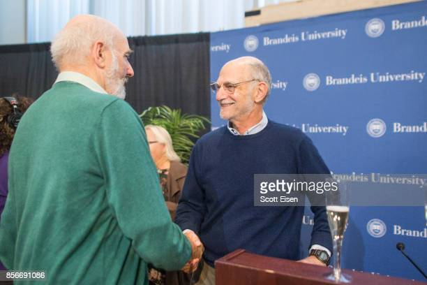 Brandeis Professor Michael Rosbash shakes hands with a colleague following a press conference where he discussed winning a Nobel Prize In Medicine on...