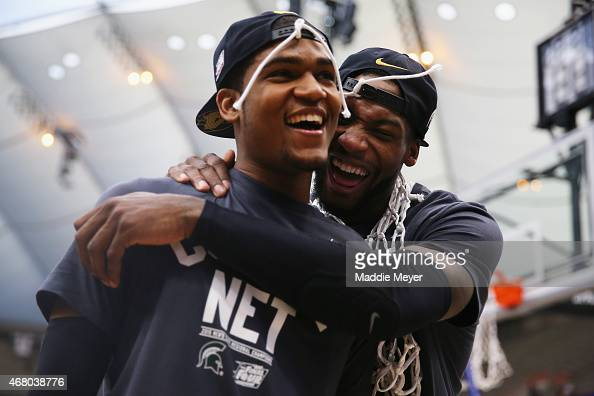 Branden Dawson and Alvin Ellis III of the Michigan State Spartans celebrate defeating the Louisville Cardinals 76 to 70 in overtime of the East...