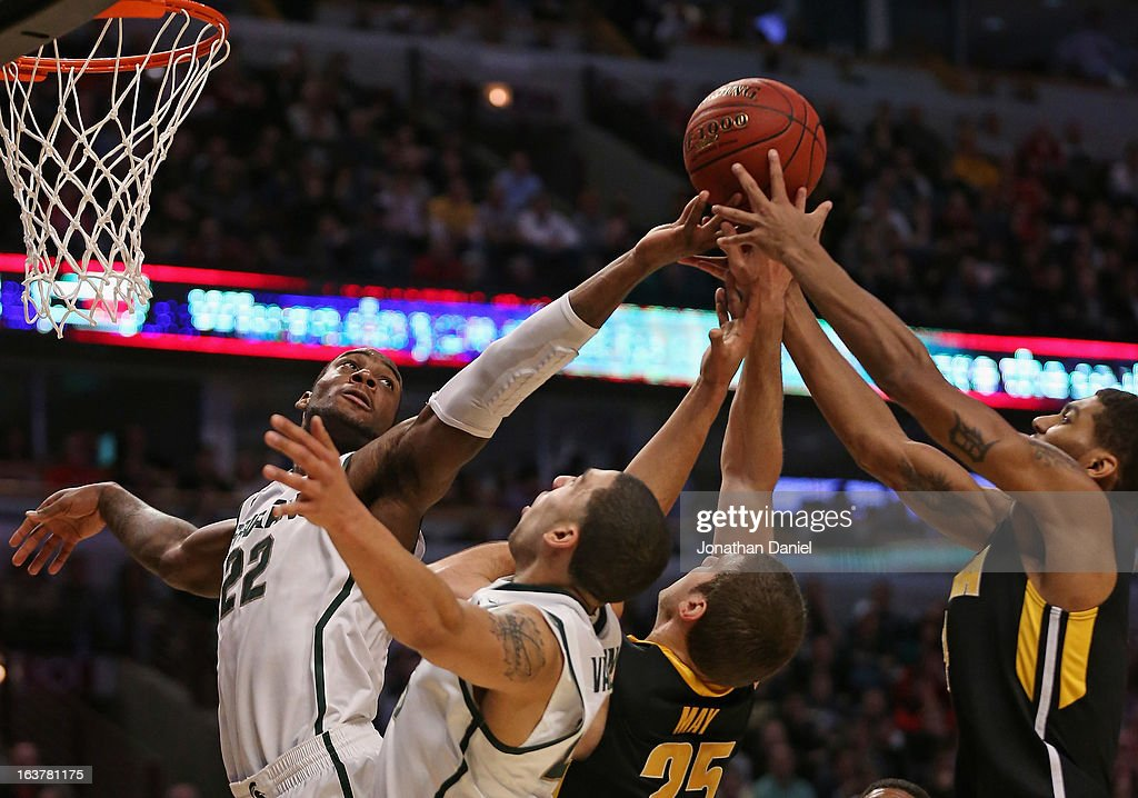 Branden Dawson #22 and Denzel Valentine #45 of the Michigan State Spartans with Eric May #25 and Roy Devyn Marble #4 of the Iowa Hawkeyes reach for the ball during a quarterfinal game of the Big Ten Basketball Tournament at the United Center on March 15, 2013 in Chicago, Illinois.