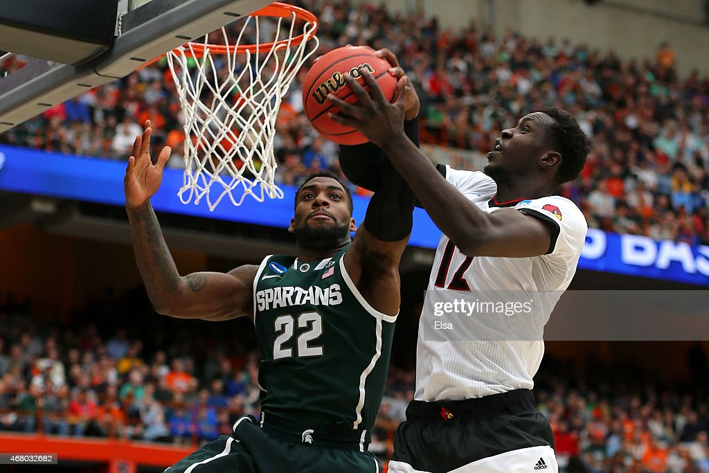 Branden Dawson of the Michigan State Spartans blocks Mangok Mathiang of the Louisville Cardinals in the second half of the game during the East...
