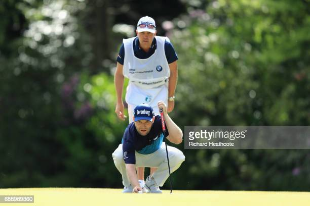 Branden Grace of South Africa and his caddie John Smart line up a putt on the 16th green during day three of the BMW PGA Championship at Wentworth on...