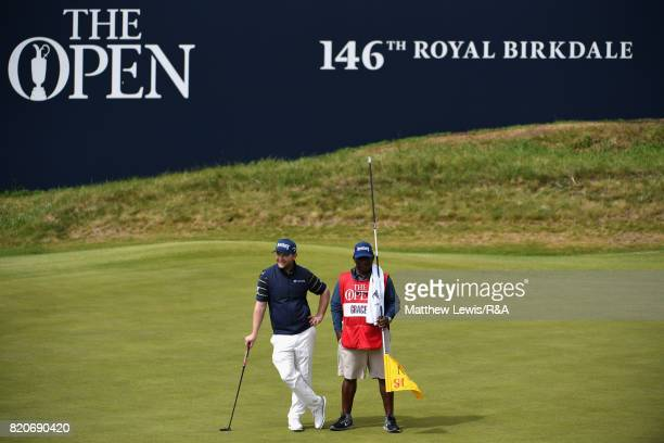 Branden Grace of South Africa and his caddie Zack Rasego on the 18th green during the third round of the 146th Open Championship at Royal Birkdale on...