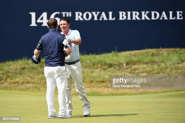 Branden Grace of South Africa and Jason Dufner of the United States shake hands on the 18th green during the third round of the 146th Open...