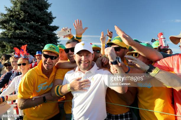 Branden Grace of South Africa and the International Team celebrates with Australian and South African fans after he had won his match with Louis...