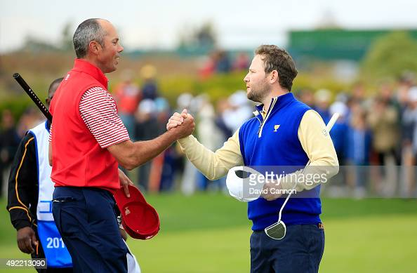Branden Grace of South Africa and the International team shakes hands with Matt Kuchar of the United States after he had beaten Kuchar by 21 during...