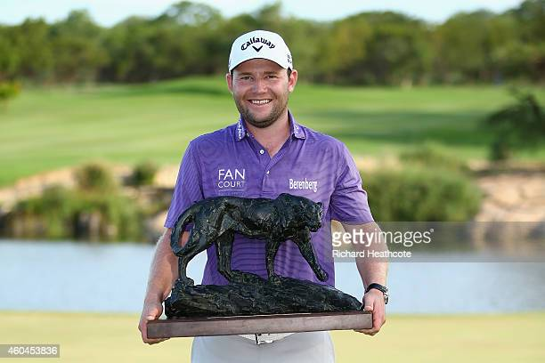 Branden Grace of South Africa holds the trophy after securing victory in the final round of the Alfred Dunhill Championship at Leopard Creek Country...