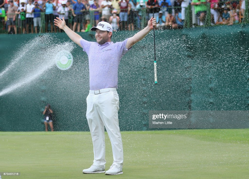 Branden Grace of South Africa is sprayed with champagne by Louis Oosthuizen and Darren Fichardt of South Africa after winning the Nedbank Golf Challenge at Gary Player CC on November 12, 2017 in Sun City, South Africa.