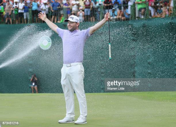 Branden Grace of South Africa is sprayed with champagne by Louis Oosthuizen and Darren Fichardt of South Africa after winning the Nedbank Golf...