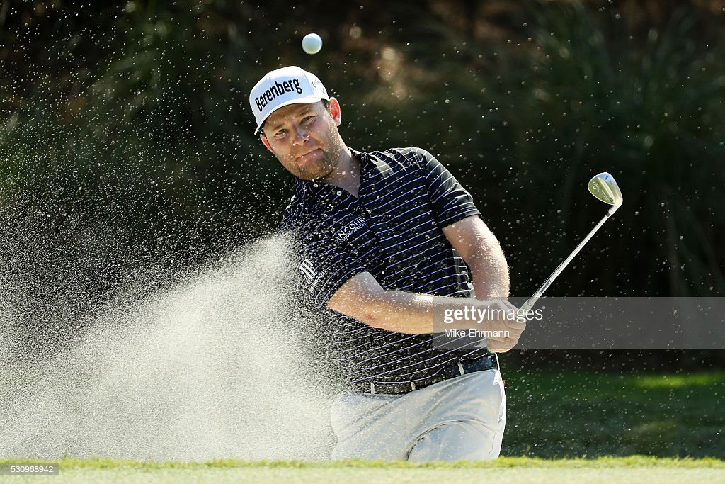 Branden Grace of South Africa plays a shot from a bunker on the 14th hole during the first round of THE PLAYERS Championship at the Stadium course at...