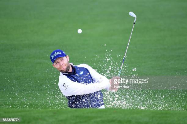 Branden Grace of South Africa plays a shot from a greenside bunker on the second hole during the first round of the 2017 Masters Tournament at...
