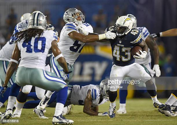 Branden Oliver of the San Diego Chargers is tackled by Damien Wilson at Qualcomm Stadium on August 13 2015 in San Diego California