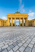 Classic view of famous Brandenburg Gate, one of the best-known landmarks and national symbols of Germany, in beautiful golden morning light at sunrise in summer, central Berlin, Germany