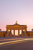 Brandenburg Gate with car lights at sunrise