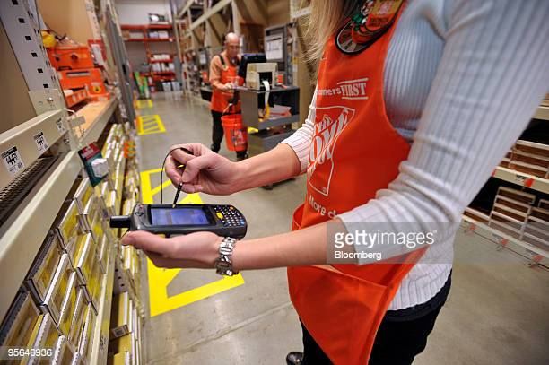 Brandi Bishop a specialty assistant manager for Home Depot checks inventory with a new portable device while fellow employee WT 'Skip' Morris...