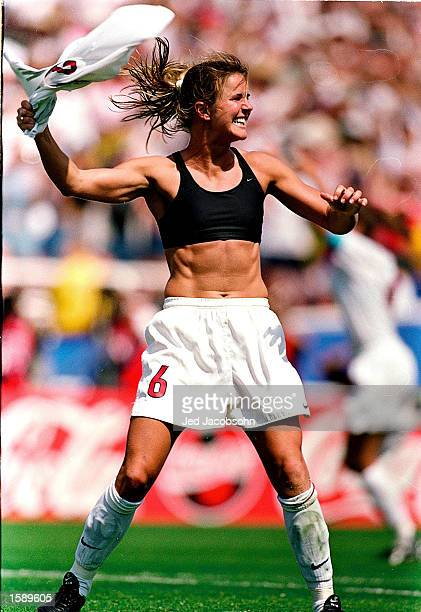 Brandi Chastain of Team USA smiles and holds up her shirt as she celebrates after making the winning goal at the FIFA Women's World Cup game against...