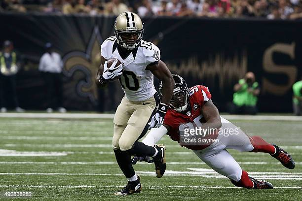 Brandin Cooks of the New Orleans Saints avoids a tackle by Jonathan Babineaux of the Atlanta Falcons during the second quarter of a game at the...