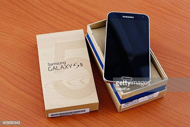 Brand-new Samsung Galaxy S5 smartphone being unpacked on wooden surface