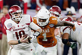 Brandon Allen of the Arkansas Razorbacks runs with the ball in the first half of the game against Shiro Davis of the Texas Longhorns at the AdvoCare...