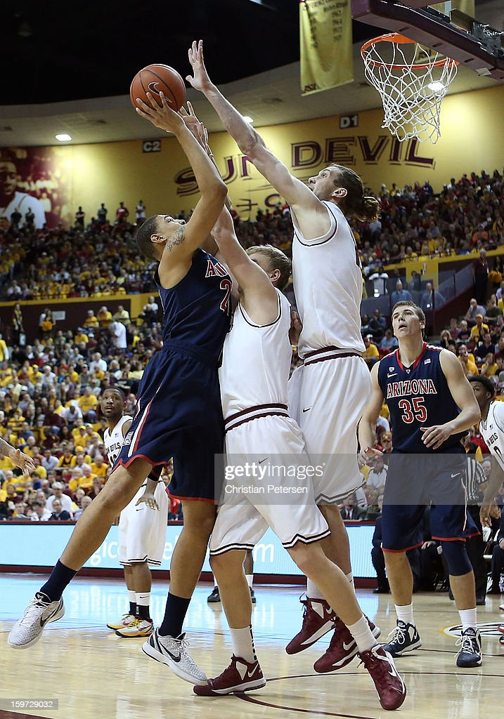 Brandon Ashley #21 of the Arizona Wildcats puts up a shot against Jonathan Gilling #31 and Jordan Bachynski #13 of the Arizona State Sun Devils during the college basketball game at Wells Fargo Arena on January 19, 2013 in Tempe, Arizona. The Wildcats defeated the Sun Devils 71-54.