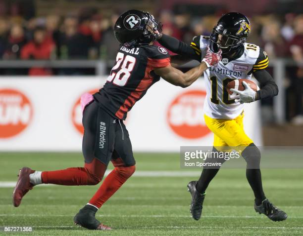 Brandon Banks of the Hamilton TigerCats breaks a tackle attempt by Corey Tindal of the Ottawa Redblacks in Canadian Football League play at TD Place...
