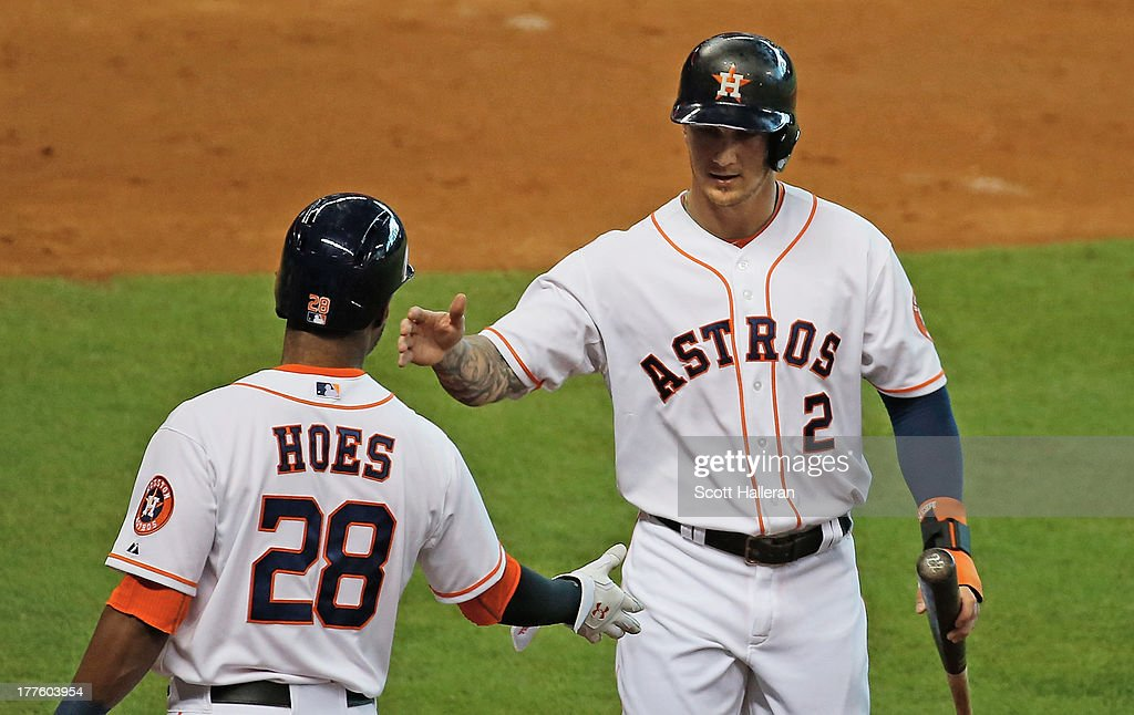 Brandon Barnes #2 and L.J. Hoes #28 of the Houston Astros shakes hands at home plate after Barnes scored a run in the second inning against the Toronto Blue Jays at Minute Maid Park on August 24, 2013 in Houston, Texas.