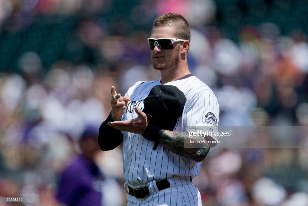 Brandon Barnes #1 of the Colorado Rockies plays paper, rock, scissors with a member of the Washington Nationals during a friendly standoff before the game started at Coors Field on July 23, 2014 in Denver, Colorado.