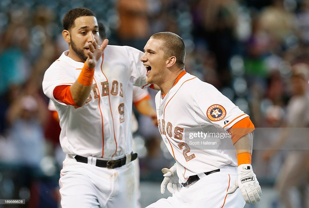 Brandon Barnes of the Houston Astros celebrates with Marwin Gonzalez after Barnes hit his RBI double in the 12th inning to defeat the Colorado...