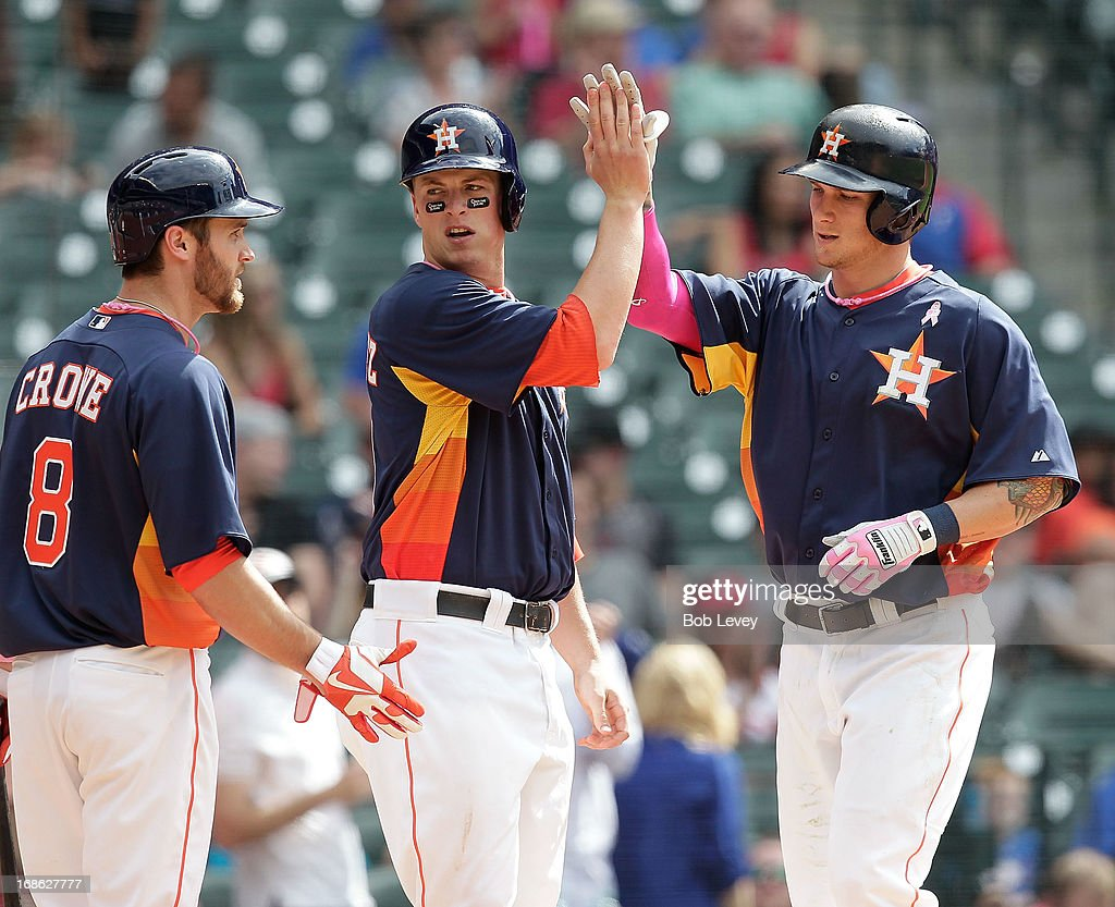 Brandon Barnes #2 of the Houston Astros receives high fives from Matt Dominguez #30 of the Houston Astros and Trevor Crowe #8 of the Houston Astros after hitting a home run at Minute Maid Park on May 12, 2013 in Houston, Texas.