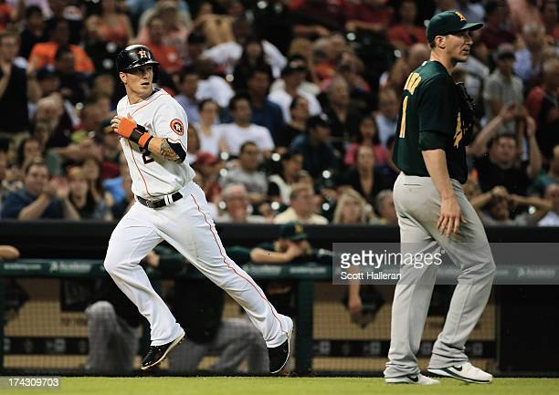 Brandon Barnes of the Houston Astros scores a run in the fifth inning as Jarrod Parker of the Oakland Athletics looks on at Minute Maid Park on July...