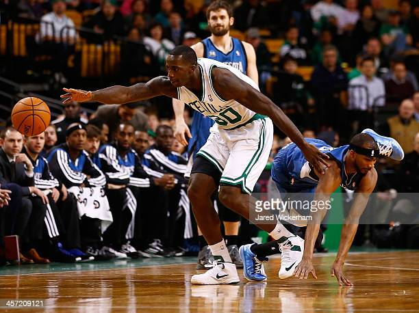 Brandon Bass of the Boston Celtics grabs a loose ball in front of Corey Brewer of the Minnesota Timberwolves in the first quarter during the game at...
