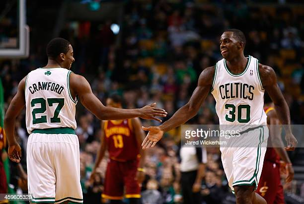 Brandon Bass of the Boston Celtics is congratulated by teammate Jordan Crawford in the second half against the Cleveland Cavalier during the game at...