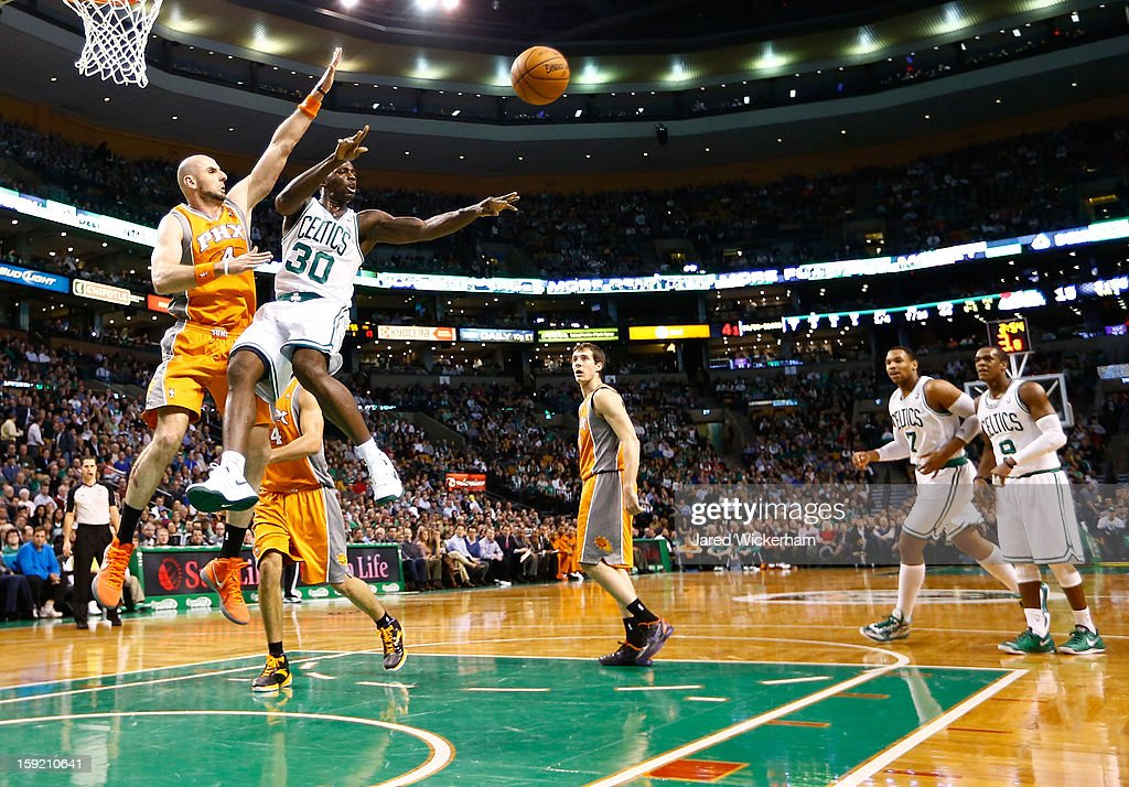 Brandon Bass #30 of the Boston Celtics makes a pass mid-air in front of Marcin Gortat #4 of the Phoenix Suns during the game on January 9, 2013 at TD Garden in Boston, Massachusetts.