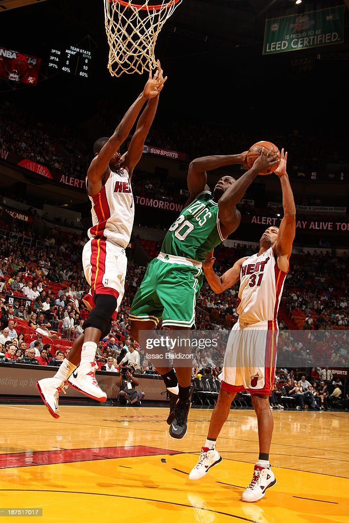 Brandon Bass #30 of the Boston Celtics shoots against Chris Bosh #1 of the Miami Heat on November 9, 2013 at American Airlines Arena in Miami, Florida.