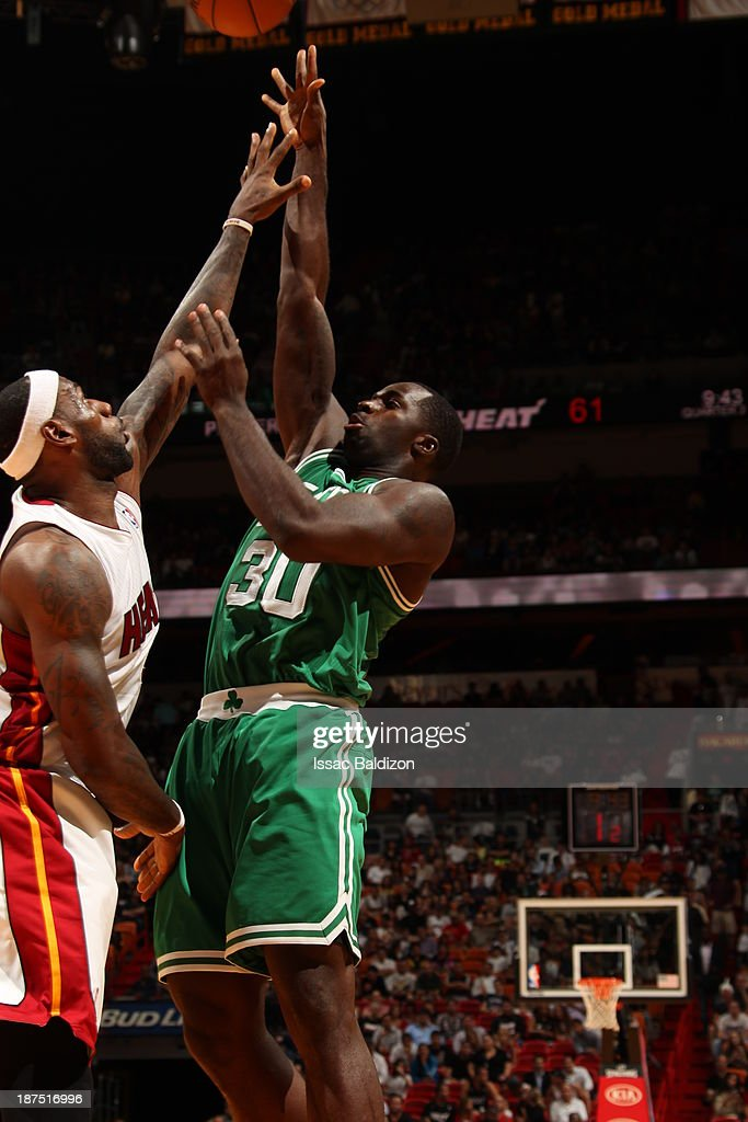 Brandon Bass #30 of the Boston Celtics shoots against LeBron James #6 of the Miami Heat on November 9, 2013 at American Airlines Arena in Miami, Florida.