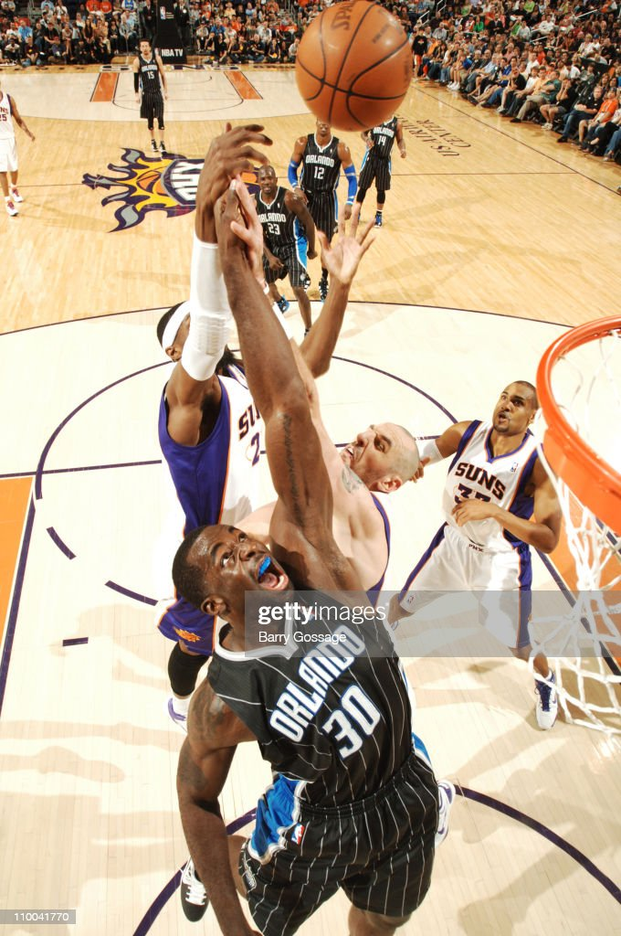 Brandon Bass of the Orlando Magic fights for a rebound with Marcin Gortat and Hakim Warrick of the Phoenix Suns in an NBA game played on March 13...