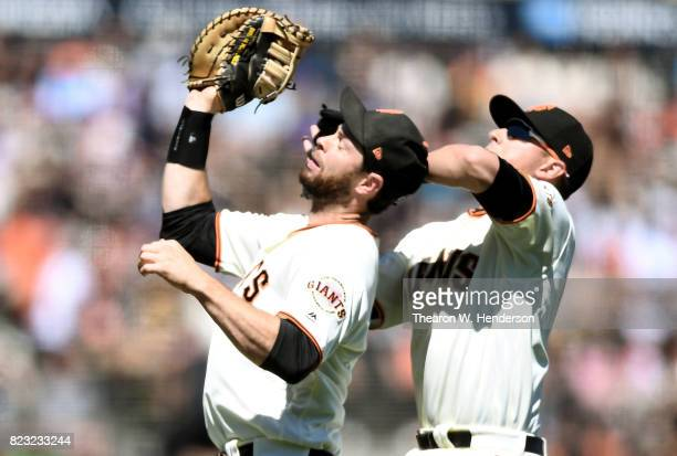 Brandon Belt and Joe Panik of the San Francisco Giants avoid colliding while Belt catches a popup off the bat of Josh Bell of the Pittsburgh Pirates...