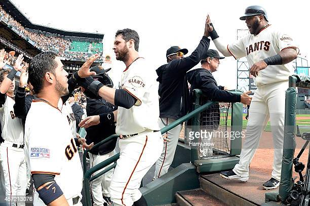 Brandon Belt and Pablo Sandoval of the San Francisco Giants celebrate with teammates after scoring in the first inning against the St Louis Cardinals...
