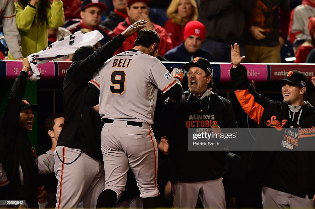Brandon Belt #9 of the San Francisco Giants celebrates with his teammates in the dugout after hitting a solo home run to right field in the eighteenth inning against Tanner Roark #57 of the Washington Nationals during Game Two of the National League Division Series at Nationals Park on October 4, 2014 in Washington, DC.