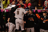 Brandon Belt of the San Francisco Giants celebrates with his teammates in the dugout after hitting a solo home run to right field in the eighteenth...