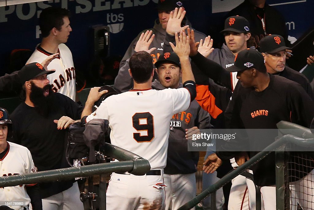 Brandon Belt #9 of the San Francisco Giants celebrates with teammates in the dugout after scoring on a single by Brandon Crawford #35 in the fourth inning of Game Two of the National League Championship Series against the St. Louis Cardinals at AT&T Park on October 15, 2012 in San Francisco, California.
